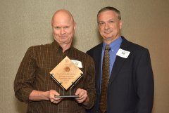 2014 Sunrise Breakfast - Steve Lloyd, left, accepts Syracuse University Sustainable Division's award from Kevin Beverine, right.