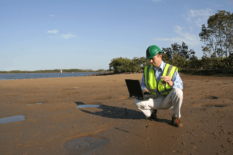 Scientist on lake shore testing water quality